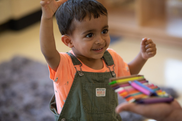 Young boy in an orange shirt and green overalls smiles and raises hands above his head