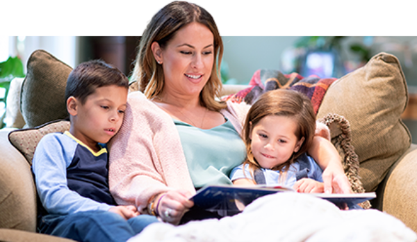 A mother reads a story to her two school-age children in a comfortable living room chair.
