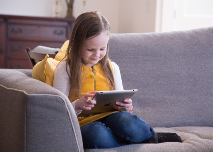 Young girl sits on couch and smiles at a tablet in her hand.